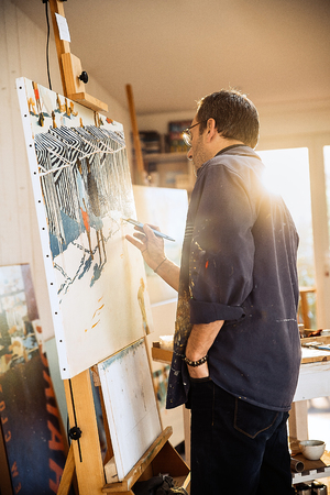 A painter in his studio working on a canvas at sunrise Imagens
