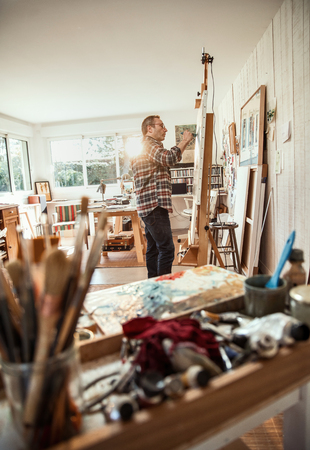 A painter in his studio working on a canvas at sunrise Stock Photo