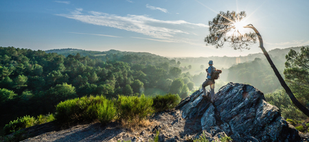 A walker on a mountain trail, looking down the valley at sunrise
