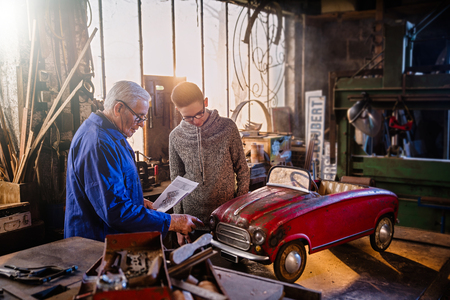 A grandfather and his grandson restoring an old pedal car Standard-Bild