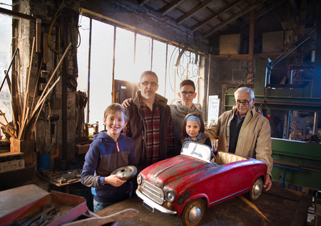Multi generation family posing in the grandfathers workshop