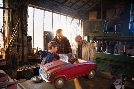Multi generation family in aDIY workshop to repair a pedal car Фото со стока