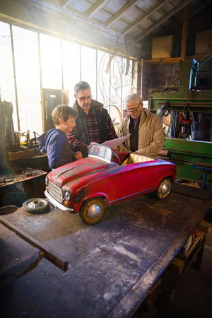 Multi generation family in aDIY workshop to repair a pedal car Stock Photo