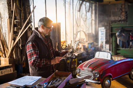 A man in his DIY workshop to repair an old pedal car Stock Photo - 115503379