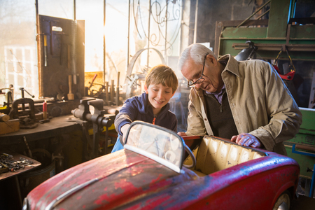A grandfather and his grandson in the DIY workshop 版權商用圖片 - 115517560