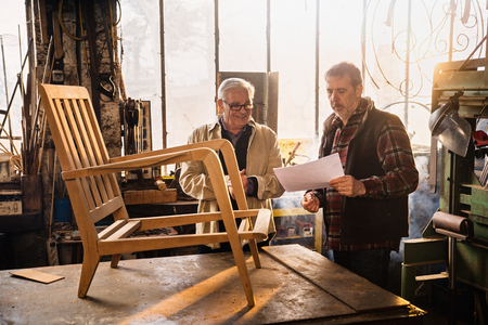 Two craftsmen in their workshop working on an armchair frame 免版税图像