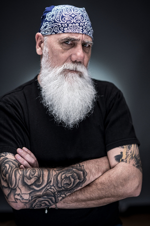 studio portrait of a senior hipster with a long white beard