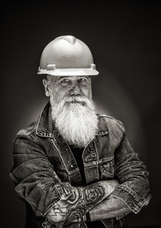 studio portrait of a hipster with a construction helmet