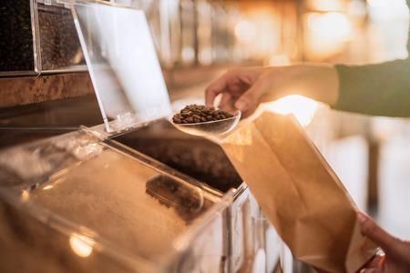 les mains des vendeurs remplissant un sac de café à partir d'un distributeur en vrac