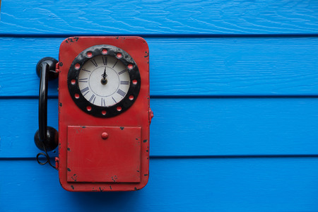 red telephone: old red telephone on blue wood wall