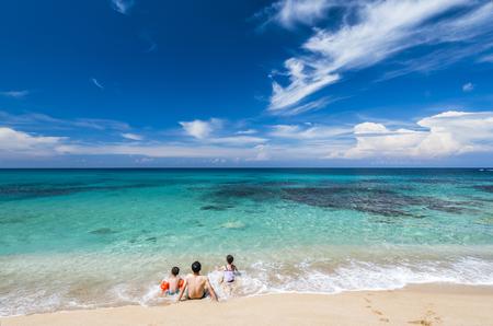 Familie mit Kindern sitzen am Strand