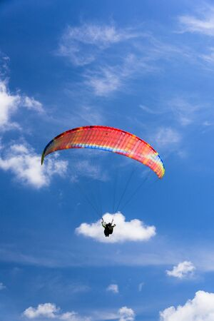 Paragliding extreme Sport with blue Sky and clouds on background Healthy Lifestyle and Freedom concept