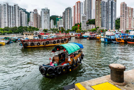 Traditional fishing trawler in the Aberdeen Bay. Famous floating village in Aberdeen is an area and town on the south shore of Hong Kong Island 新闻类图片