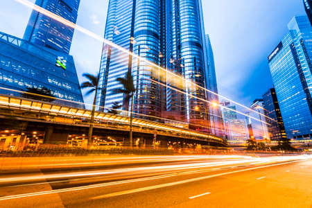 Street traffic in Hong Kong at night. Office skyscraper buildings and busy traffic on highway road with blurred car light trails. Hong Kong.