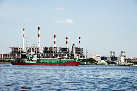 chao praya: Electric power refinery plant in Thailand foreground with red green ship in the Chao praya river. Stock Photo