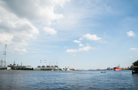 chao praya: The panoramic view of the electric refinery plant and big red logistic ship in Chao Praya river, Bangkok.