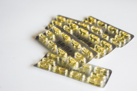 Yellow Capsule pills and package use in pharmaceutical manufacturing, drug, medicine, garlic oil, fish liver oil. Stock Photo