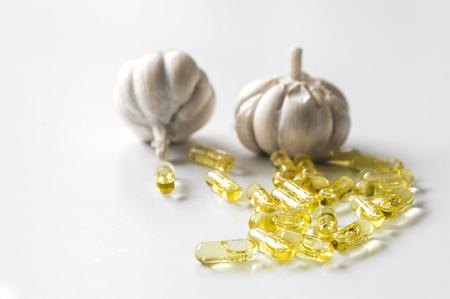 Garlic oil capsules on white background