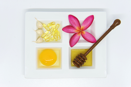 white mask: Set of healthcare beauty treatment, garlic capsule, honey and egg yoke on white ceramic plate and wooden spoons.