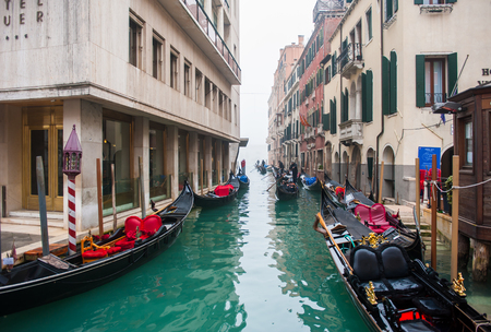 sight seeing: VENICE, ITALY - 26 DECEMBER, 2015: Tourists ride on a gondola to do sight seeing the colorful architectural in narrow canal and grand canal. Editorial