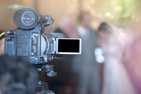 shooting bride and groom with video camera in wedding ceremony, focus at camera.