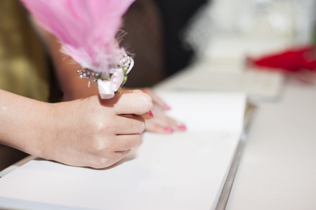 Woman's hand signing guest book in wedding party with pen decorated with feather.