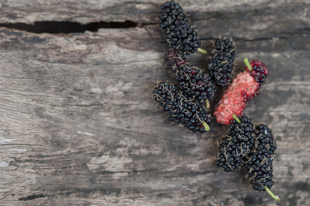 Mulberry red and black berry fruit in wooden spoon locates on a surface vintage wooden background