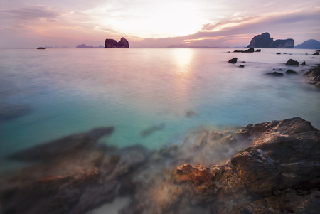 Sun rise on the rock beach on Ngai island in southern sea of Thailand. Mountain background against the colorful red sky and emerald turquoise blue water. Slow shutter speed shooting seascape.