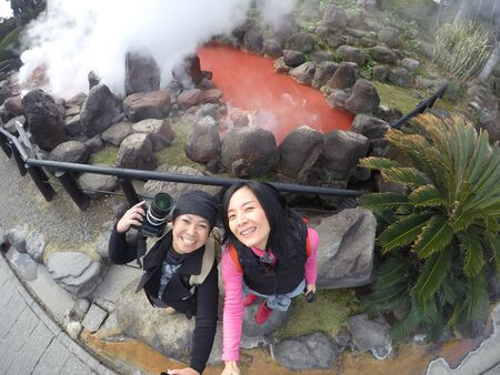 Two Asian tourist women take a photo at Hot spring water (Hells), red pond in Umi Jigoku at Beppu, Oita-shi, Kyushu, Japan. Shooting with superwide angle, action camera.