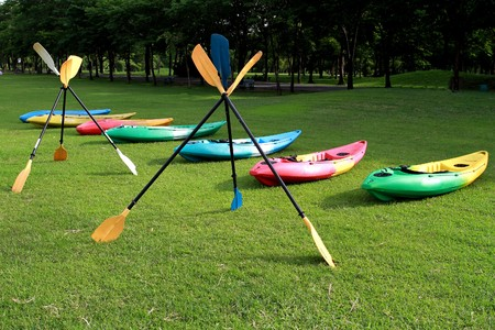 colorful canoe and oars on green garden