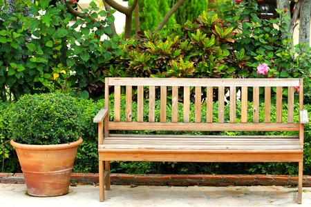 garden furniture: Wooden park bench in the garden Stock Photo