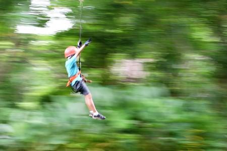Little boy crossing ravine on rope