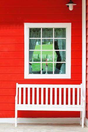glasscheibe: Weißer Stuhl gegen weiße Fenster und Rote Wand  Lizenzfreie Bilder