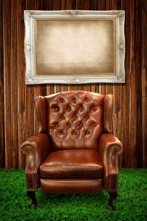 leren bank: Lederen sofa op groene gras en foto frame tegen houten muur