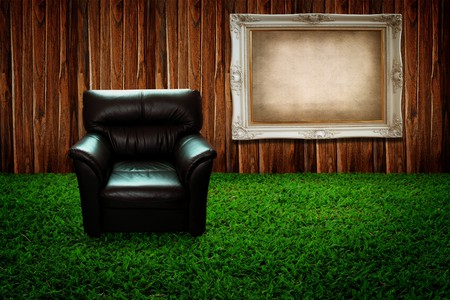 Leather sofa on green grass and photo frame against wooden wall photo