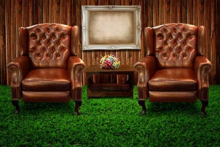leren bank: Twee leerbank op groene gras en foto frame tegen houten muur