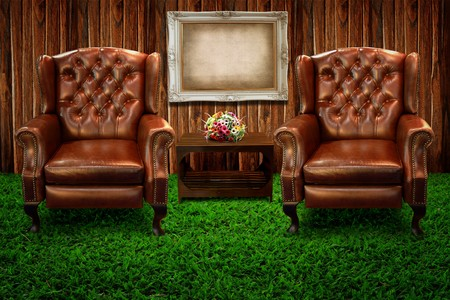 Two leather sofa on green grass and photo frame against wooden wall