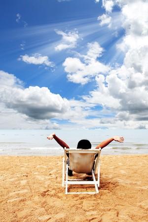 Zaken man ontspannen op het dek op het strand Stockfoto