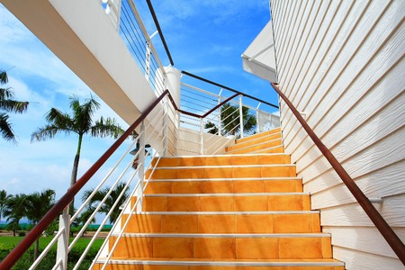 Orange staircase and white wooden wall