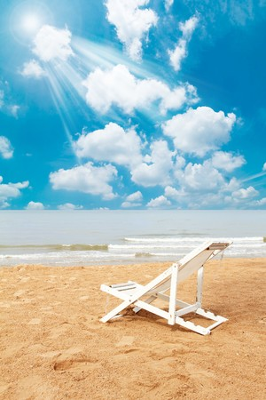 White deck chair on beach and blue sky photo