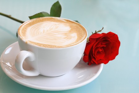Close-up of coffee cup with rose flower photo