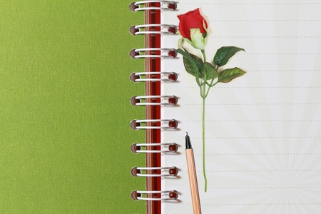 Open notebook and red rose photo