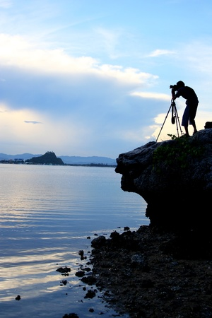 personas tomando agua: Silueta de fotógrafo en tierra la puesta del sol Foto de archivo