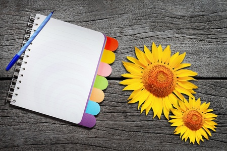 note book: Open note book and sun flower on wood background  Stock Photo