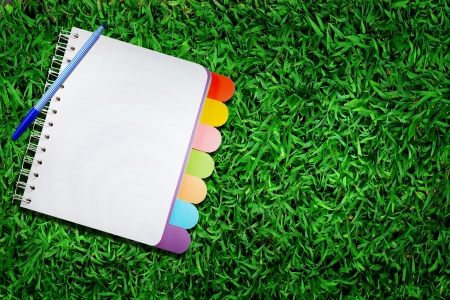 Open note book on green grass   photo