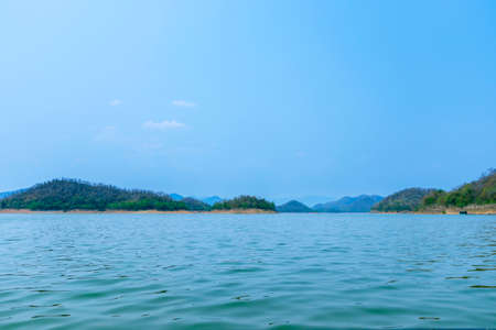 The lake scenery with mountains behind under the blue sky
