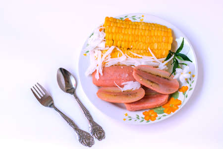 Food on a plate with cutlery on a white background