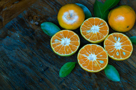 Fresh fruit oranges with leaves on wooden background
