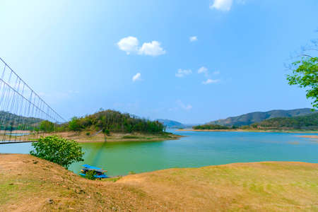 Lake and mountain scenery with beautiful blue sky and white clouds at Kaeng Krachan Dam in Thailand.