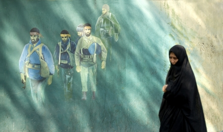 martyr: veiled woman by martyr mural in tehran iran